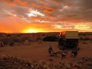 Safari truck camping in the sunset in the Namibian desert